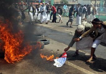 Manifestanti bruciano le bandiere americane