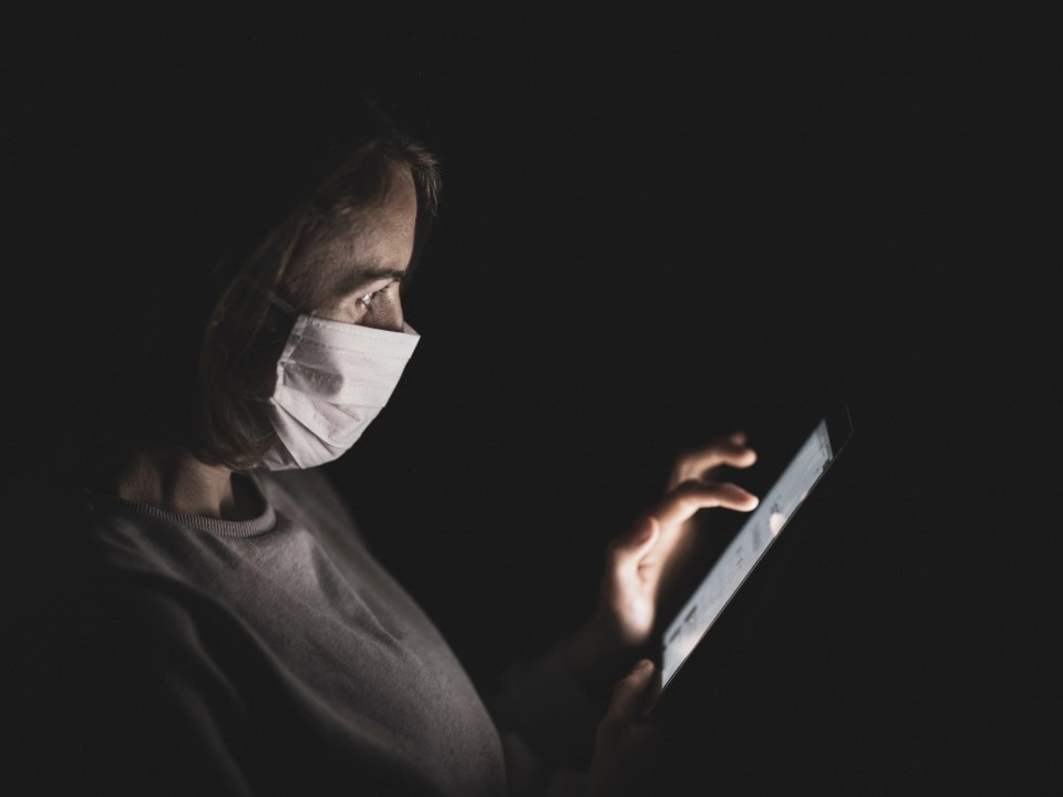 Girl with mask holding a tablet