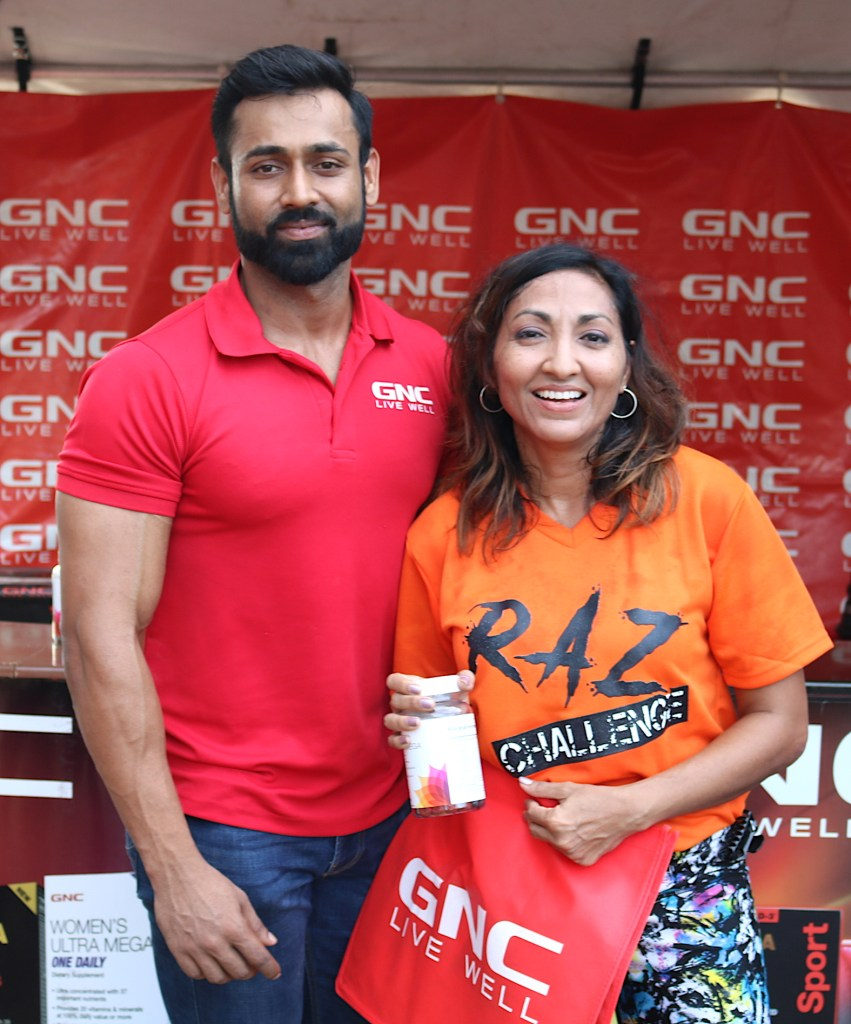 GNC Brand Ambassador Nicholas Ramoutar, left, presents Plank Challenge winner Heather Dass with GNC merchandise at the 2018 Raz Challenge in Gasparillo.