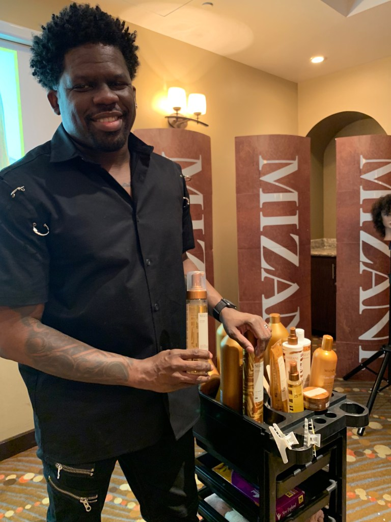 Mizani Educator Jamal Edmonds shows off the Mizani Bond pHorce products.