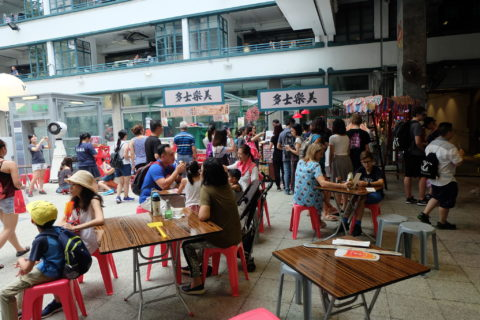 A crowd of people move through what seems to be the courtyard of a mall, with families sitting at tables in the foreground and throngs of people going in and out of stores in the background.