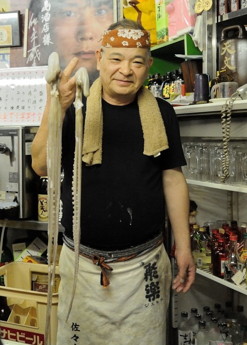 Photograph of a man holding octopus tentacles