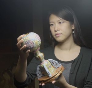 Christie's specialist Ivy Chan examines a Chinese vase