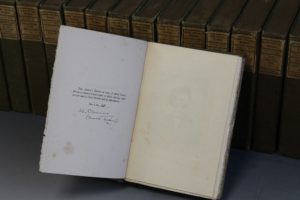 Copy of Vol I 'The Innocents Abroad' Vol I, signed 'S L Clemens' (Mark Twain) in front of other tomes in the collection