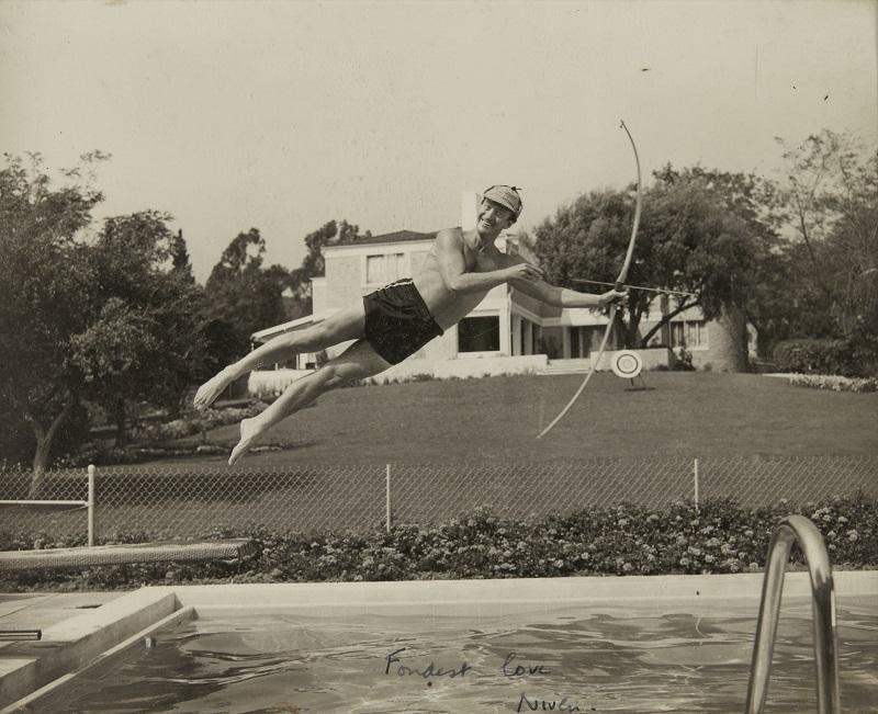 Photograph of David Niven jumping into swimming pool