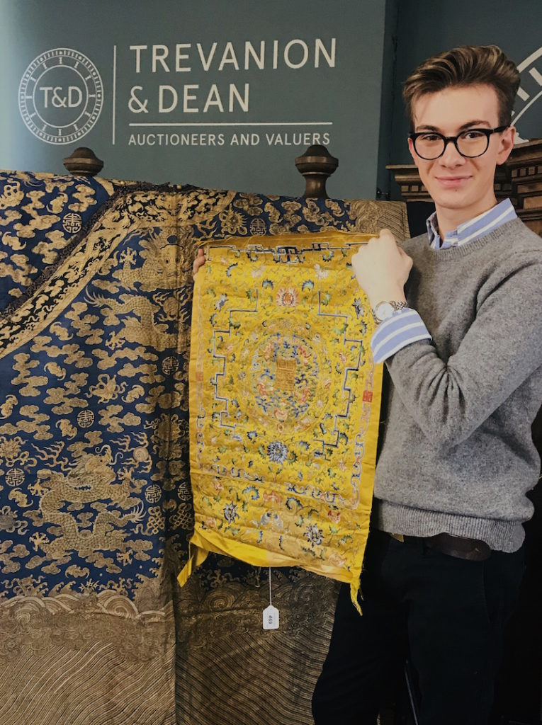 Auctioneer Ashley Jones with the Chinese silk cover that sold for £6500
