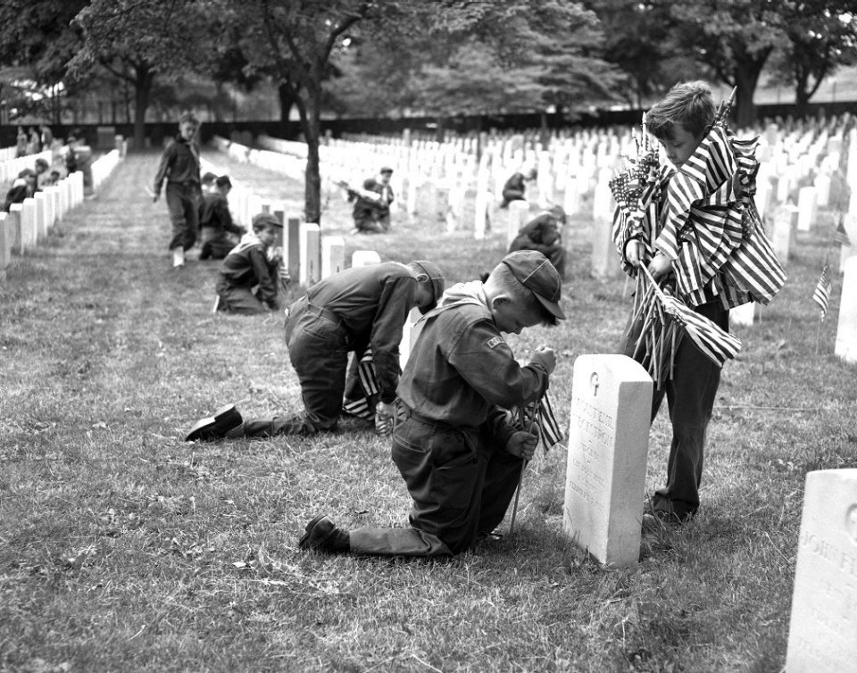 Tomas Gregson, 10, and William Rush, 8, both Boy Scouts of Brooklyn, decorate graves in the Cypress Hills National Cemetery. According to this photo's original caption, more than 500 Boy Scouts and their leaders particpated in the annual ceremony of decorating 19,000 graves.