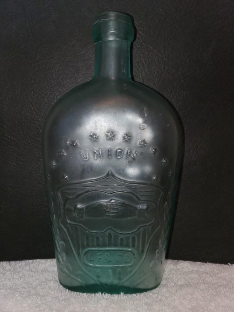 """Frasco de whisky """"Águila de manos unidas con bandera"""", 1860-1870."""