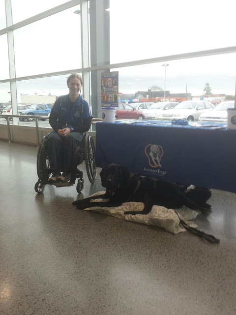 Antnz on left in wheelchair, ADNZ Ben lying on a blanket in front of an ADNZ display table
