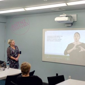 Annette Hansen standing to the left of a paused image of a NZSL video about Deaf Communications