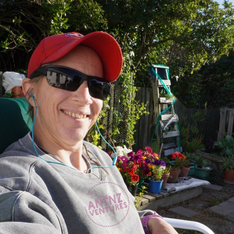 Selfie of Antnz, smiling wearing sunglasses and a red cap to the left of frame, a colourful garden in background to the right.