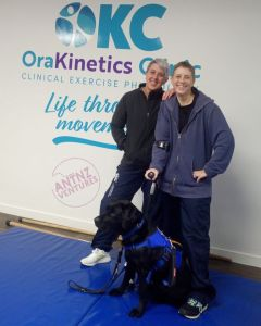 Antnz (right) and Tasha standing in front of an OraKinetics logo. ADNZ Raven is sitting in front of them looking off camera.