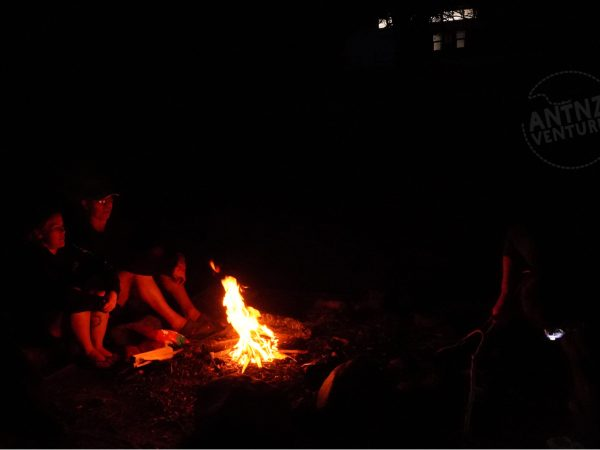 A picture taken at night of a campfire. The campground is in the foreground center of the picture. Natt and Peter sit to the left of the fire, to the right of the fire you can see a torch. In the the background are the lights at the hut.