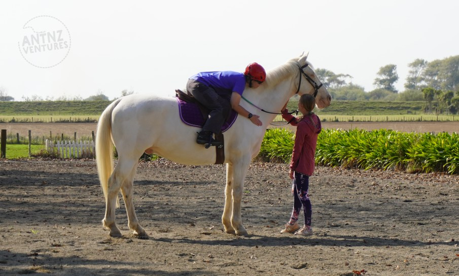A large white horse stands sideways in the middle of the frame. On the horse Antnz sits, leaning fully forward on the horses neck, patting the base of the neck of the horse. Another woman is standing by the horses head patting the horses neck.