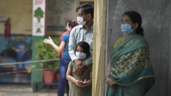 25 जून को दिल्ली के अरुणा आसफ अली रोड पर एक स्कूल में कोविद -19 परीक्षण के लिए नमूने देने के लिए मरीज अपनी बारी का इंतजार करते हैं