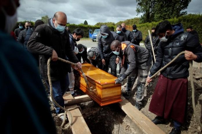 ताहरा एसोसिएशन के स्वयंसेवकों ने 38 वर्षीय अबुकर अब्दुलाही काबी, एक मुस्लिम शरणार्थी, जो कोरोनोवायरस बीमारी (COVID-19) से मृत्यु हो गई थी, के ताबूत को पेरिस, फ्रांस के पास ला कौरन्यूवे में एक कब्रिस्तान में एक कब्रिस्तान में दफनाने के दौरान दफनाया। 17, 2021. चित्र 17 मई, 2021 को लिया गया। रॉयटर्स/बेनोइट टेसियर