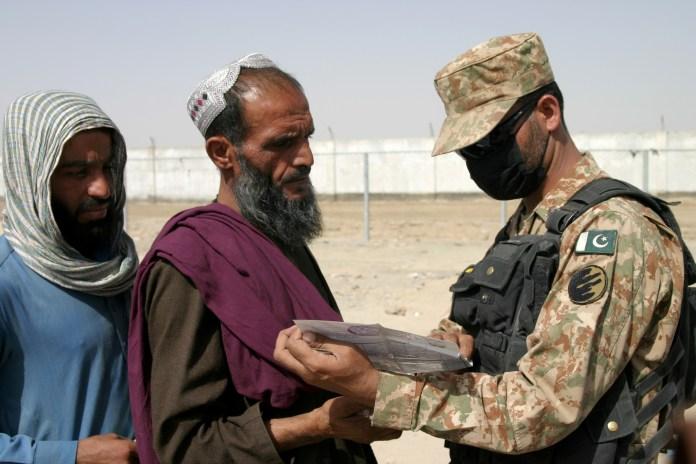 27 अगस्त, 2021 को पाकिस्तान-अफगानिस्तान सीमावर्ती शहर चमन में फ्रेंडशिप गेट क्रॉसिंग पॉइंट पर एक पाकिस्तानी सैनिक अफगानिस्तान से आने वाले लोगों के दस्तावेजों की जांच करता है। रॉयटर्स/सईद अली अचकजई/फाइल फोटो