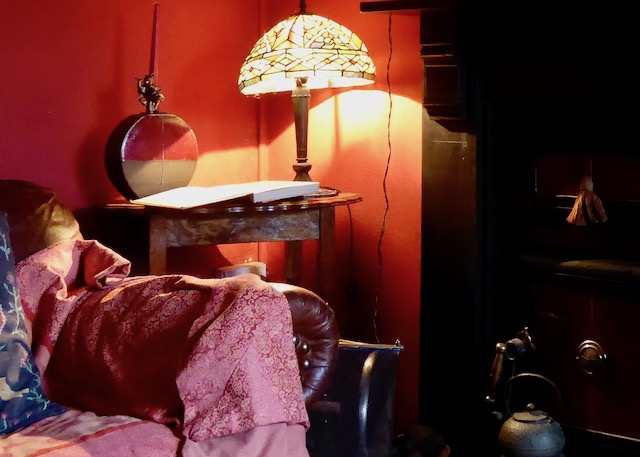 old fireplace with sofa, lamp  in red room, country house