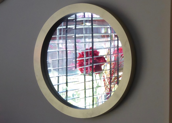 round mirror reflecting red flower and blinds