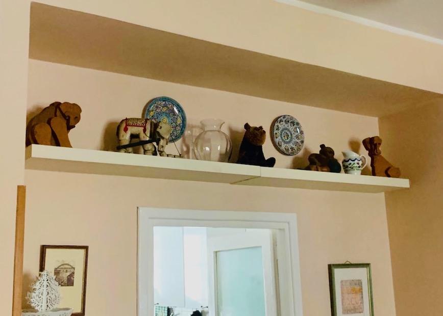 shelf with ornaments above door in italy
