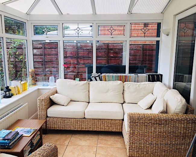cream sofa in conservatory with books