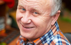 Older man wearing plaid shirt smiling