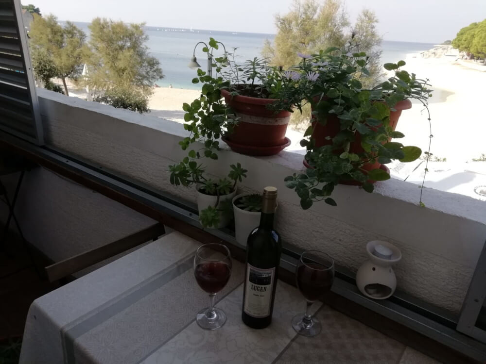 Bottle of red wine, two glasses on table with sea view in the background