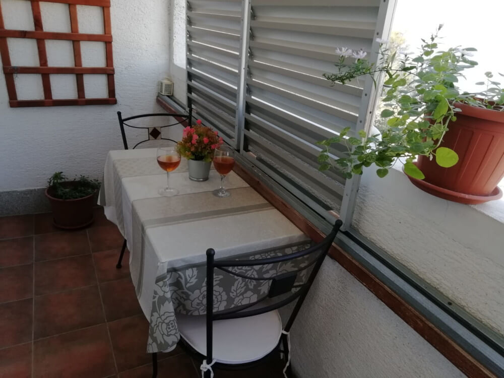 Balcony with furniture: table, two chairs in Apartmani Smiljana in Primošten