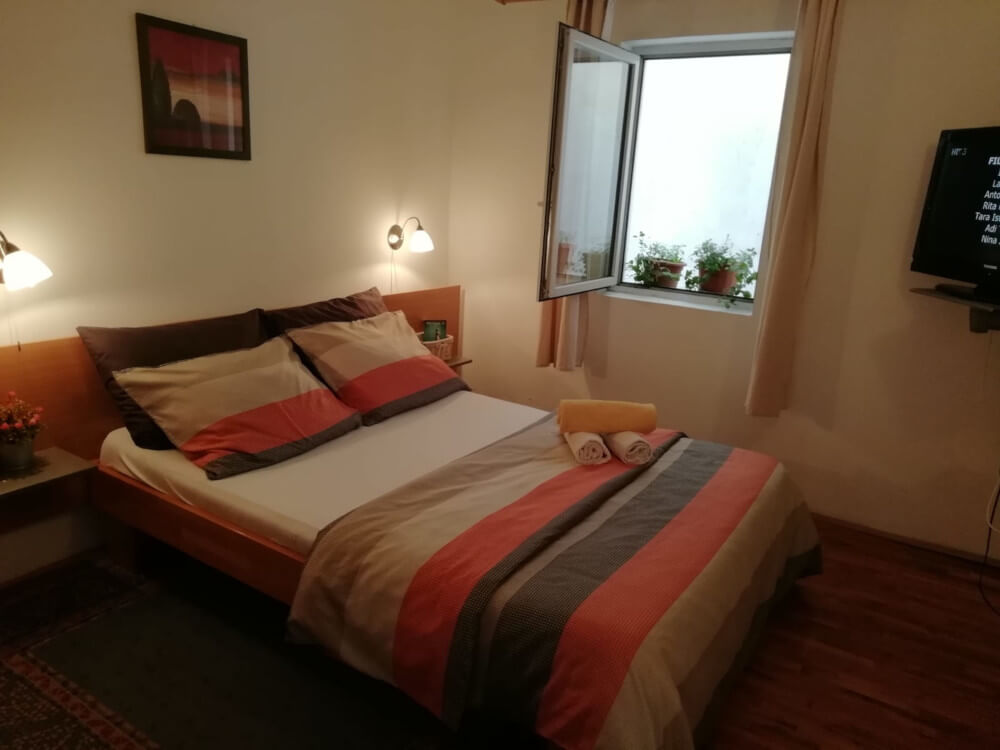 Double bed with cover and folded towels in Apartment 3 in Apartmani Smiljana in Primošten