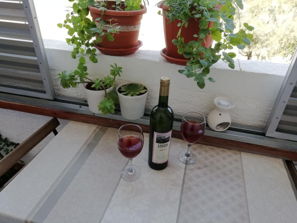 Bottle of wine, two glasses on balcony table in Apartment 2 in Apartmani Smiljana Primošten