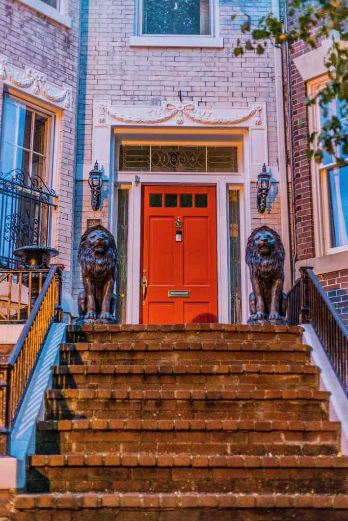 Stairs to a Red Front Door Framed By Lion Statues