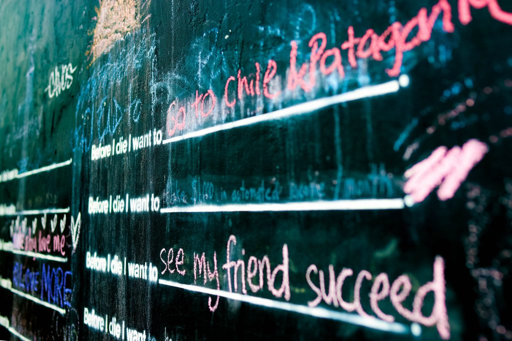 See my friend succeed written in pink chalk on the Before I Die Wall Mural on South Congress In Austin, Texas