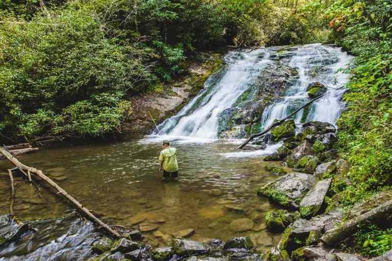 Man wearing a yellow shirt fishing at the base of Indian Creek Falls