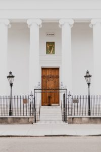 Iron picket fence protect a white building with a brown door and two lampposts.