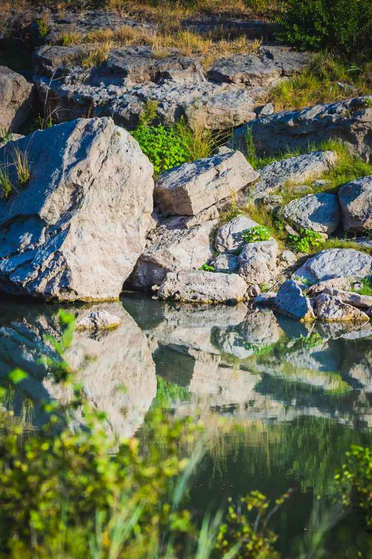 calm creek reflects large, white, boulders on the shore.
