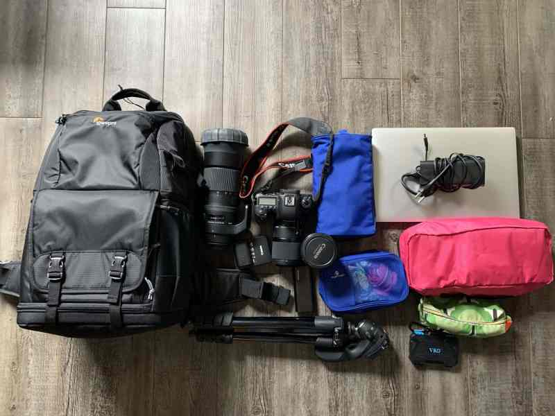 Flat Lay of black Lowepro Backpack with photography and travel equipment