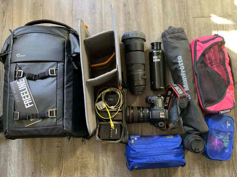 Small black camera backpack carrying camera equipment and a few other items
