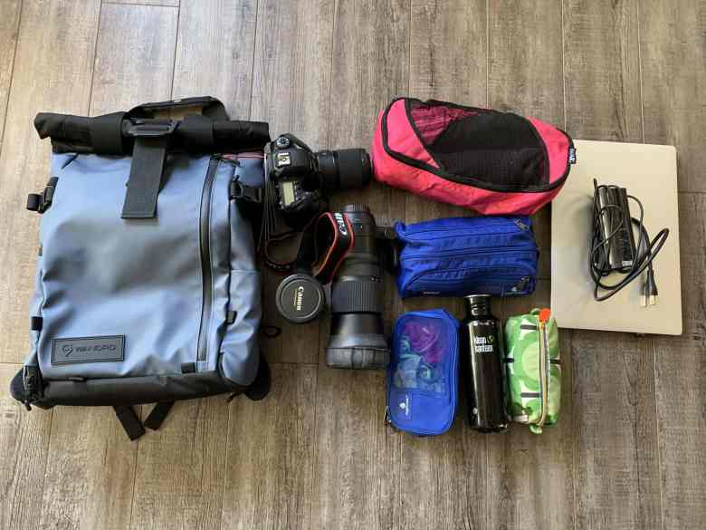 Flat Lay of blue soft shell camera Backpack with photography and travel equipment