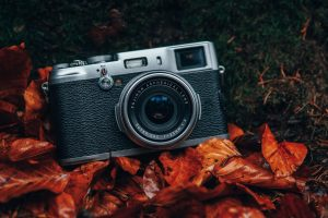 Point and shoot camera on bed of orange leaves -  Beginner Tips Banner