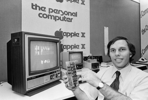 B&W photo of businessman in store holding Apple II peripheral