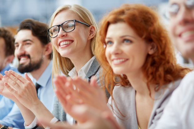 Photo of happy business people applauding at conference, focus on smiling blonde