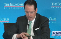 Uma captura de tela de um vídeo do C-SPAN em que o CEO da AT&T recebe uma chamada ao vivo no palco.