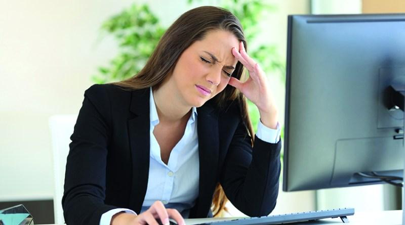 Frau mit Migräne am Arbeitsplatz