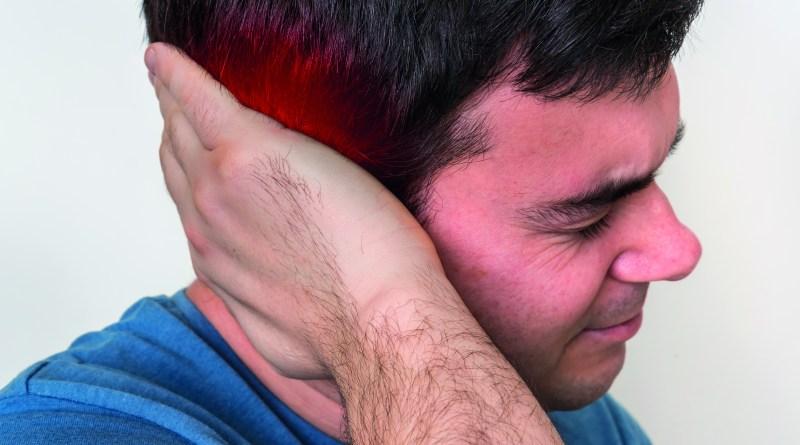 Ohrenschmerzen. Mann hält sich das Ohr wegen Ohrenschmerzen.