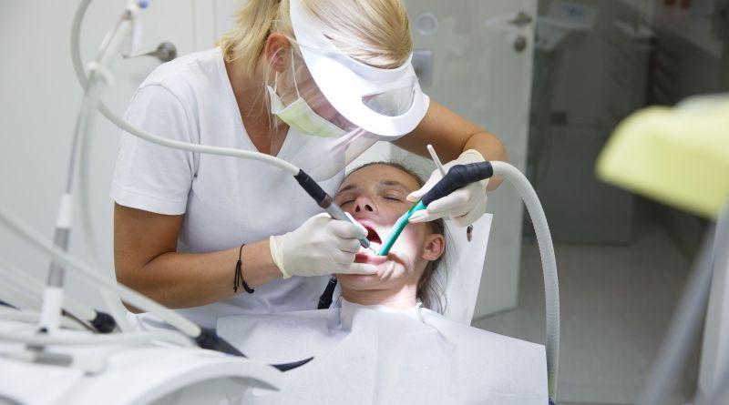 Mann mit offenem Mund bei Zahnärztin. Zahnbehandlung. Gesundes Zahnfleisch