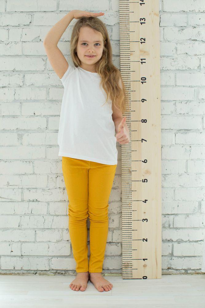 Schulstart. Mädchen steht an Mauer vor Messlatte