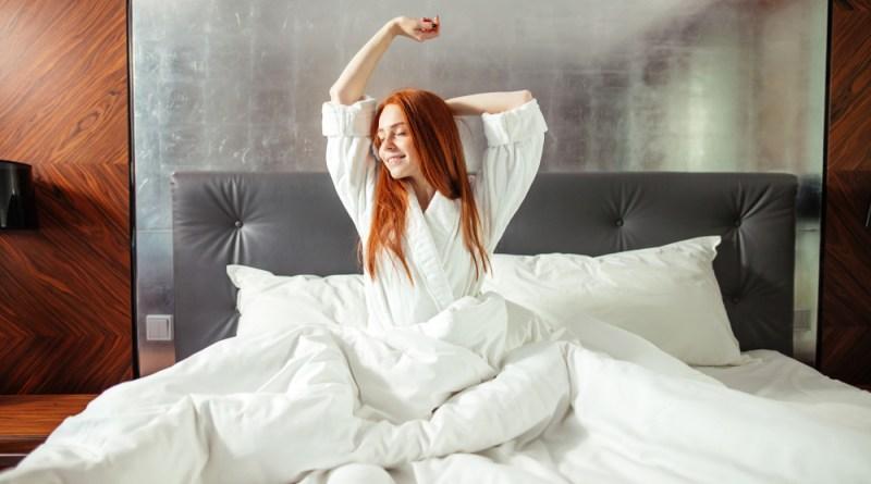 Frau wacht glücklich und ausgeschlafen in Bett auf. Schlaf