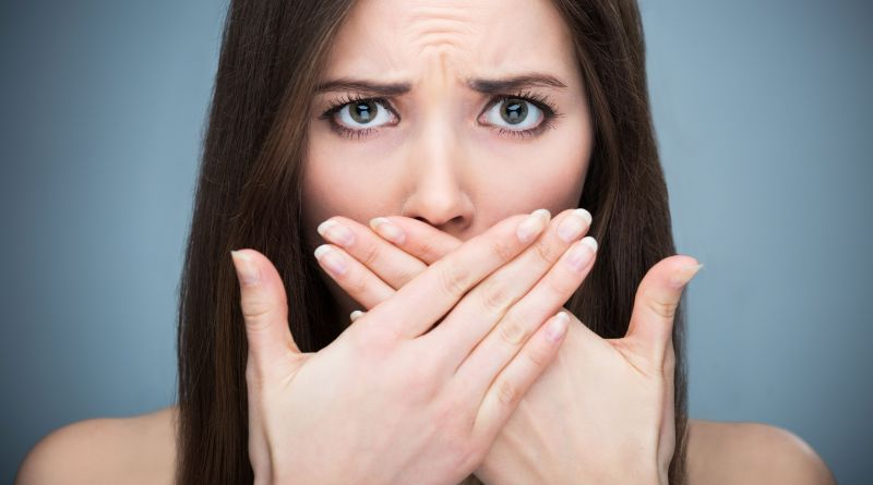 Frau hält sich verzweifelt Hände von den Mund. Mundgeruch