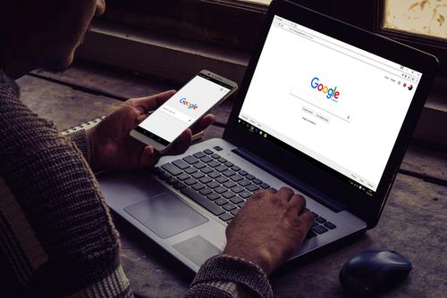 Mann googelt am Laptop und Smartphe. Dr. Google