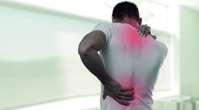 Mann greift sich auf Rücken und Nacken. Hat Schmerzen. Wärmetherapie